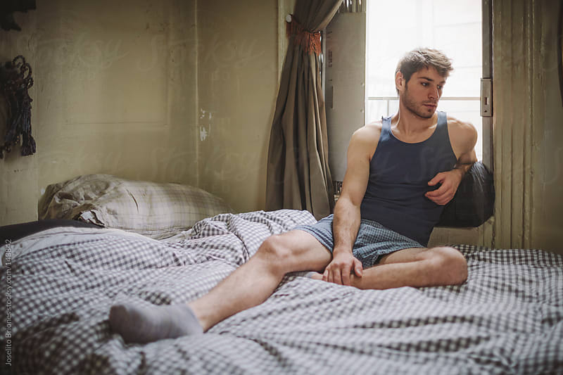 Man in Reflective Mood in Bed at Home by Joselito Briones for Stocksy United