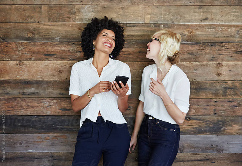 Portrait of millennial businesswomen laughing looking at phone by Trinette Reed for Stocksy United