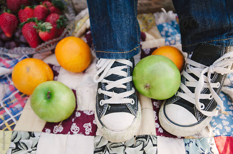Young boy feet with fruit dropped around by Kristin Rogers Photography for Stocksy United
