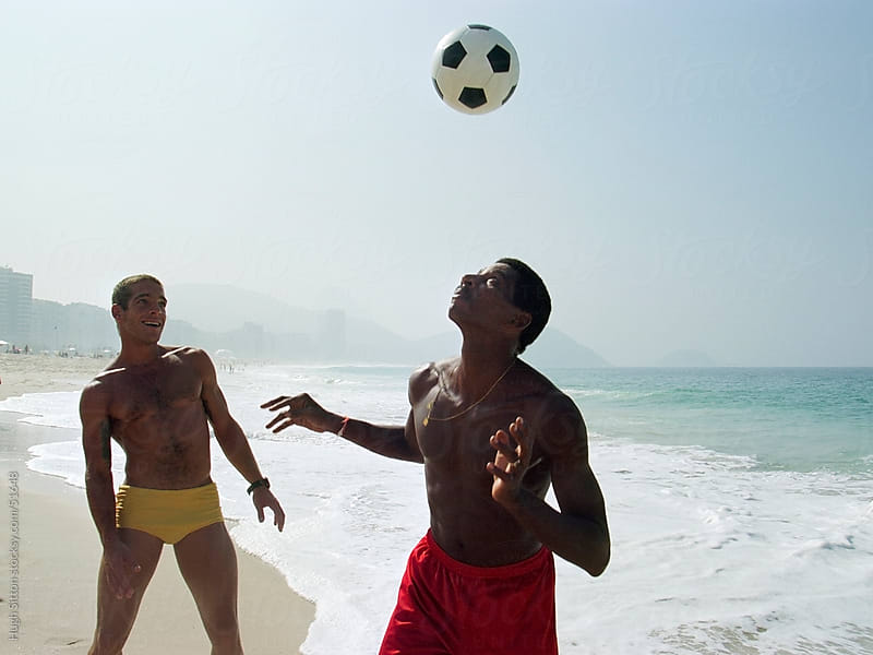 Two men playing soccer on Ipanema beach. Rio de Janeiro. Brazil by Hugh Sitton for Stocksy United