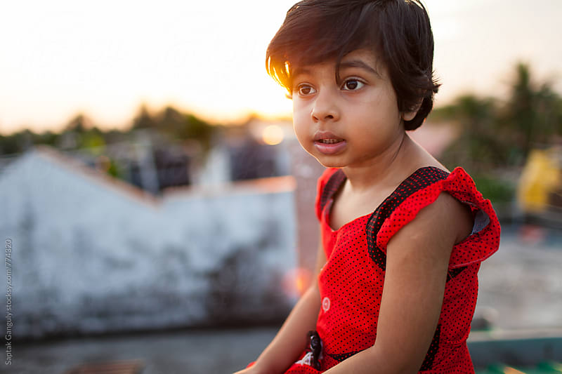 Portrait of cute little girl sitting on rooftop at sunset by Saptak Ganguly for Stocksy United