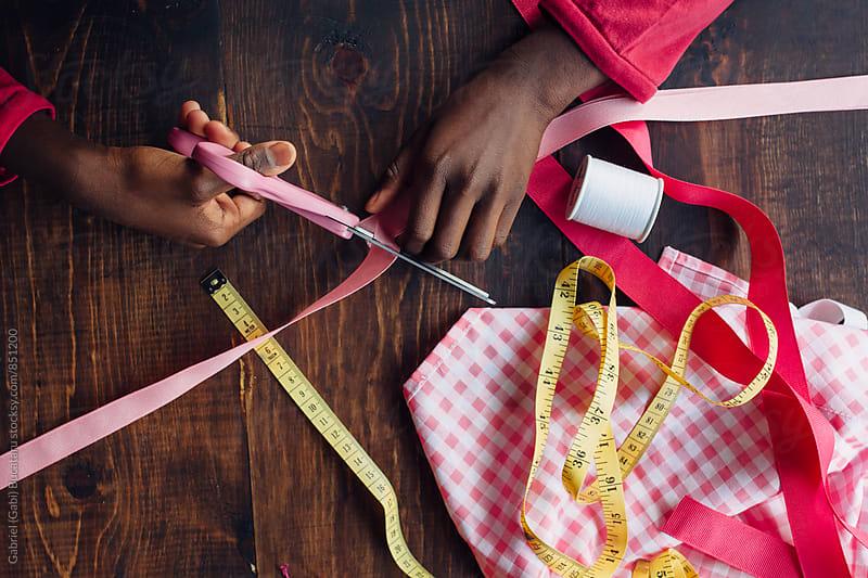 African American girl's hands cutting a pink ribbon by Gabriel (Gabi) Bucataru for Stocksy United