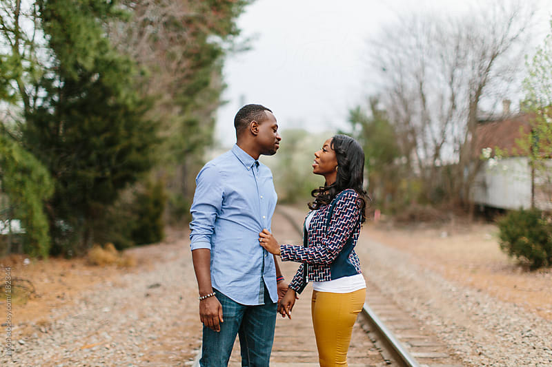 Trendy and stylish African-American couple holding hands while walking along train tracks by Jakob for Stocksy United