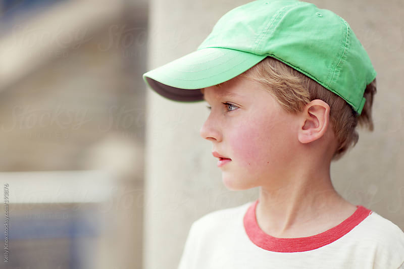 portrait of a boy wearing a baseball cap by Kelly Knox for Stocksy United