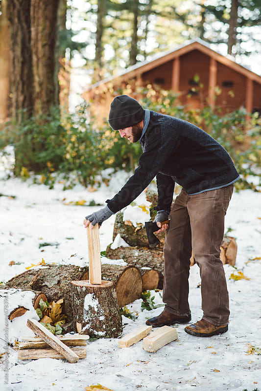 Man chopping wood outside a cabin in the snow by Kate Daigneault for Stocksy United