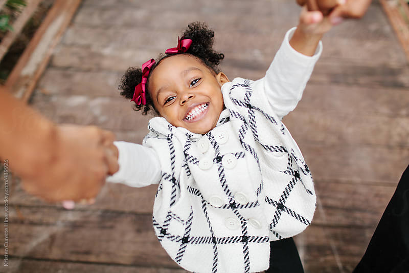 Candid portrait of a smiling 2 year old girl holding her parents hands by Kristen Curette Hines for Stocksy United