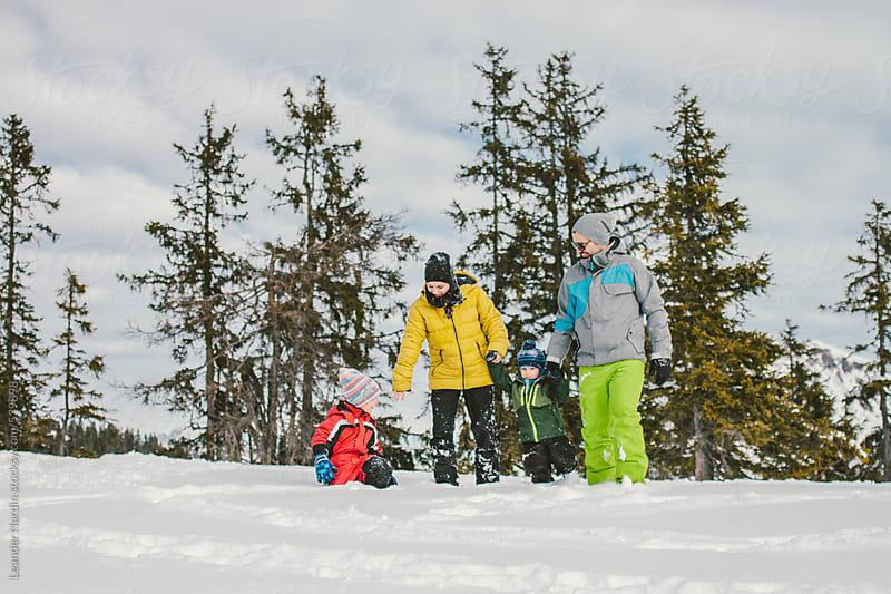 family walking in snow in alpine landscape by Leander Nardin for Stocksy United