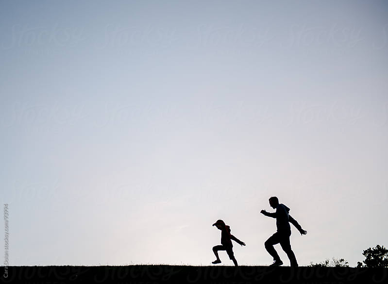 Silhouette of a father and son walking together across a field at sunset by Cara Dolan for Stocksy United