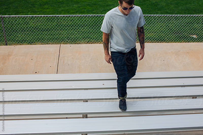 Man walking up bleachers by Gabrielle Lutze for Stocksy United