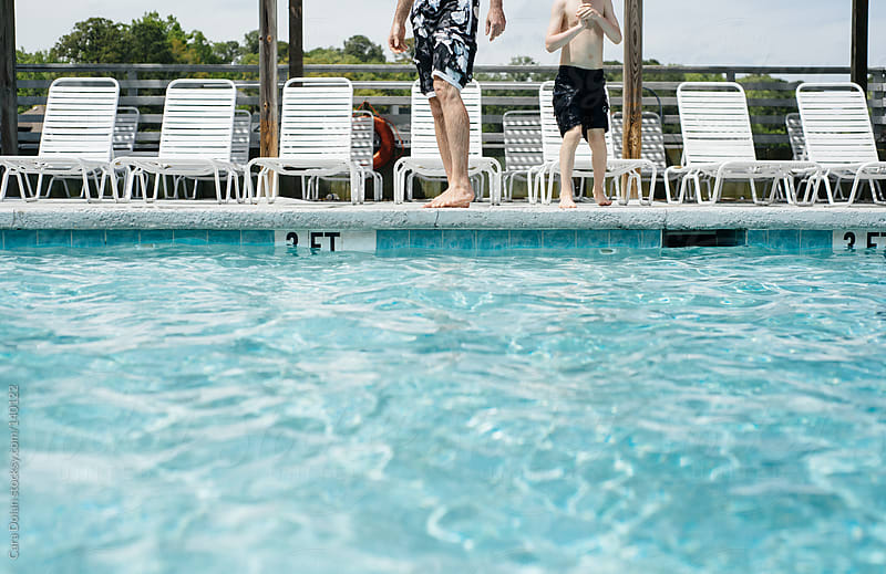 Boy and his father stand at the edge of a swimming pool, ready to jump in by Cara Dolan for Stocksy United
