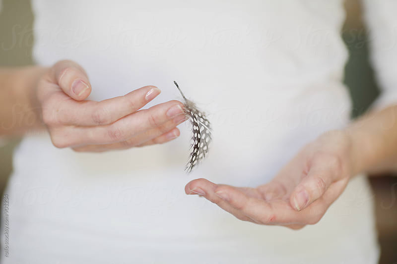 Woman's hands with plume by rolfo for Stocksy United