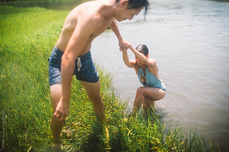 Young man helps young woman out of mucky water by HOWL for Stocksy United