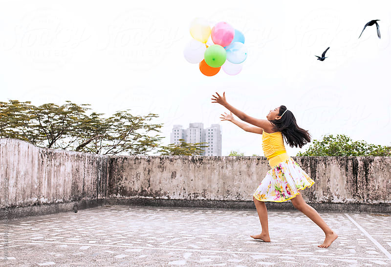 A Girl is playing with colorful balloons in old Kolkata City,India by PARTHA PAL for Stocksy United
