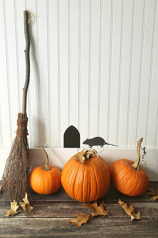 Pumpkins and broom leaning against wall by Sandra Cunningham for Stocksy United