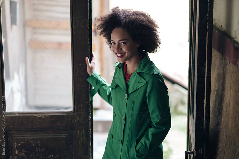 Portrait of a Beautiful Smiling Woman in Green Trench Coat by Branislav Jovanović for Stocksy United