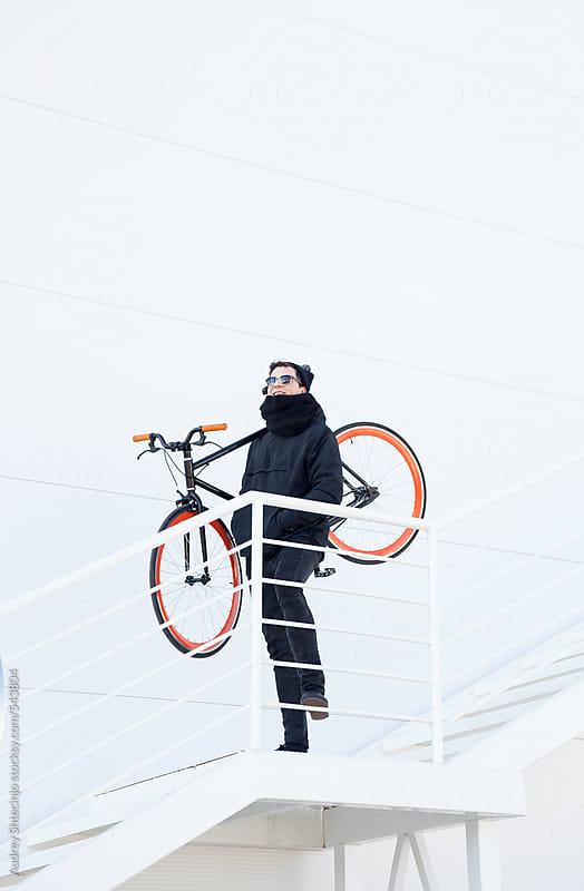 Young hip guy in black with his bike standing on white staircase. by Audrey Shtecinjo for Stocksy United