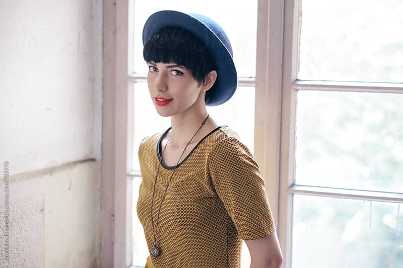 Beautiful Stylish Woman with Blue Hat Standing in Front of a Window by Branislav Jovanović for Stocksy United