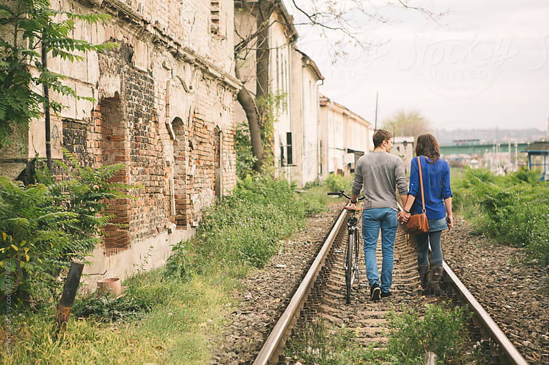 Couple Walking Down the Railroad by Lumina for Stocksy United