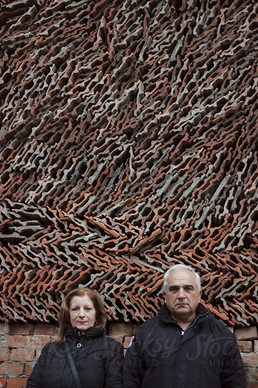 An old couple standing in front of pile of tiles by Jovana Rikalo for Stocksy United