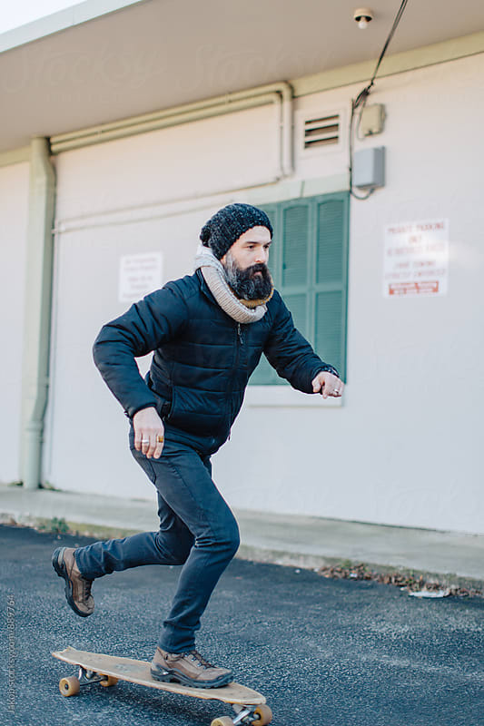 Cool bearded man riding a skateboard by Jakob for Stocksy United