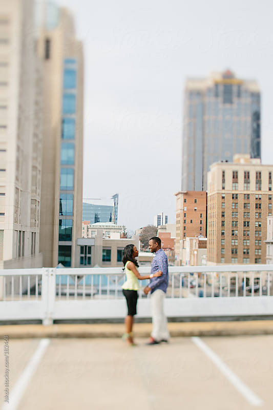 African American couple in love standing on top of a parking garage with skyscrapers behind them by Jakob for Stocksy United