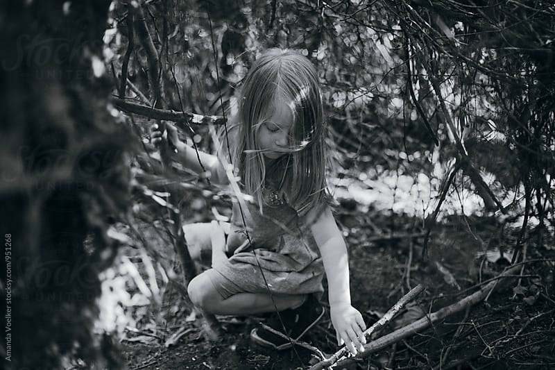 black and white of a little girl sitting thoughtfully in the woods by Amanda Voelker for Stocksy United
