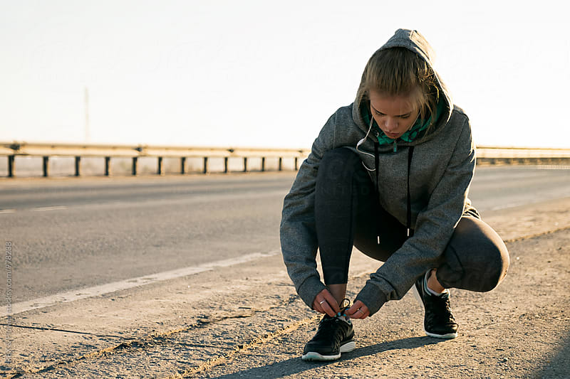 Young woman in hood tying laces on road by Danil Nevsky for Stocksy United