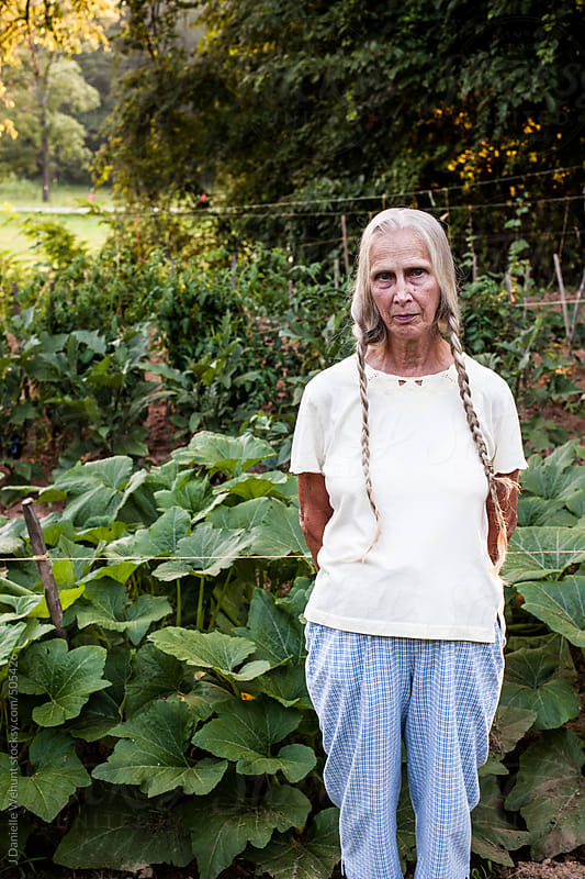 Elderly woman with blonde braids standing in front of vegetable garden by J Danielle Wehunt for Stocksy United