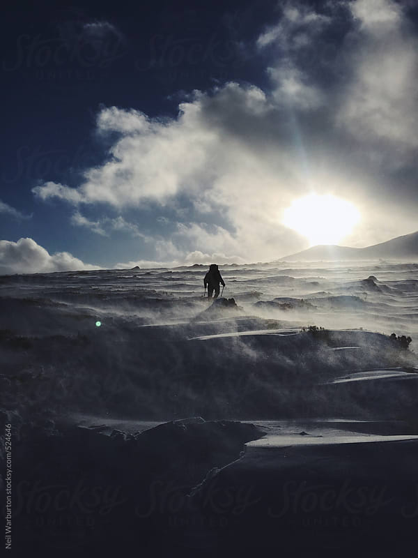 A silhouette of a hiker in a winter storm by Neil Warburton for Stocksy United