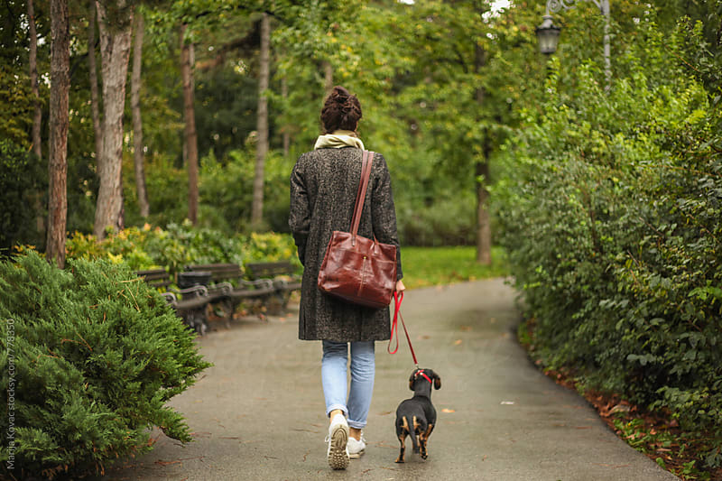 Woman walking with a dog by Marija Kovac for Stocksy United