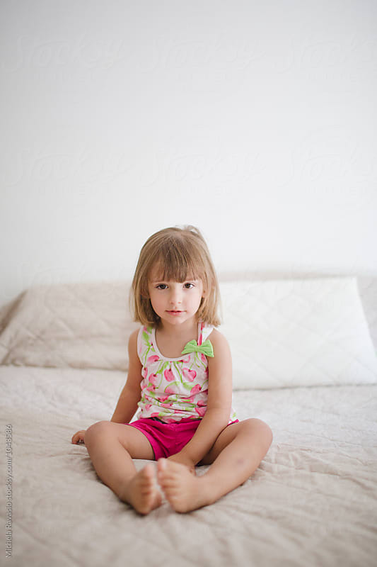 Baby girl sitting on the bed by michela ravasio for Stocksy United