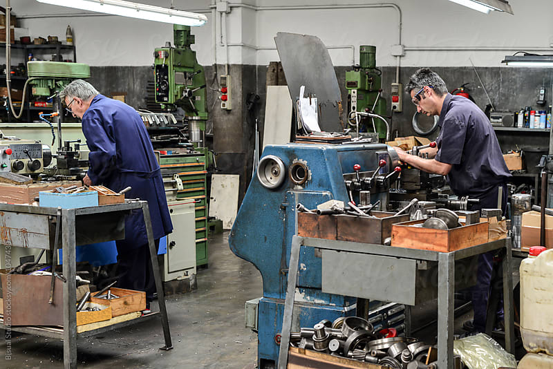 Two men working in a metal workshop by Bisual Studio for Stocksy United