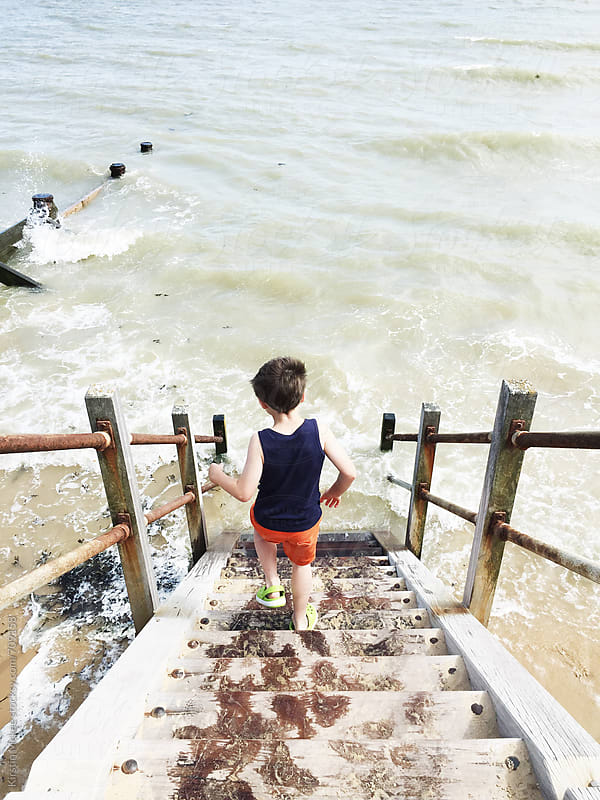 Boy running down steps into sea by Kirstin Mckee for Stocksy United
