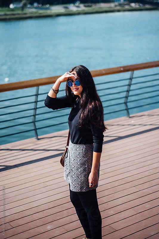 Young woman standing by the river dock by Katarina Simovic for Stocksy United