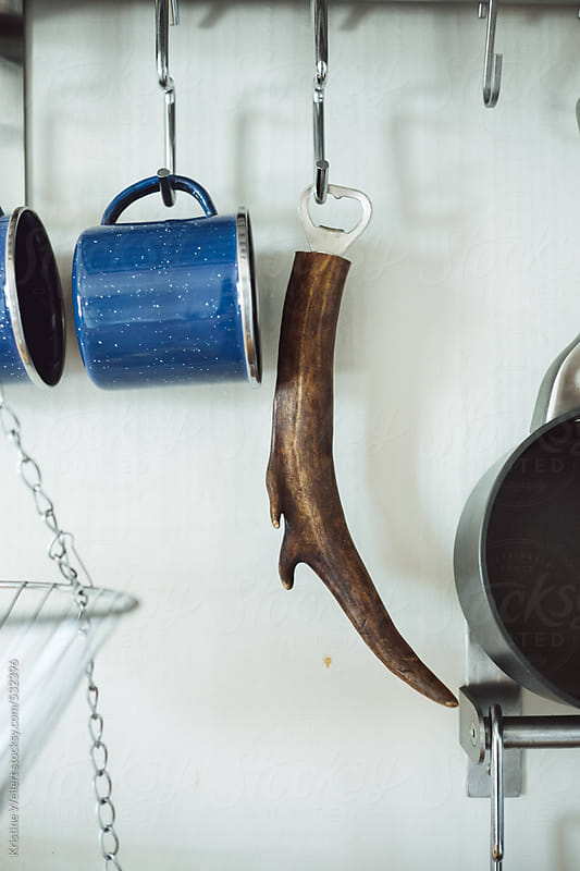 And antler bottle opener and tin mugs hanging on a kitchen wall by Kristine Weilert for Stocksy United