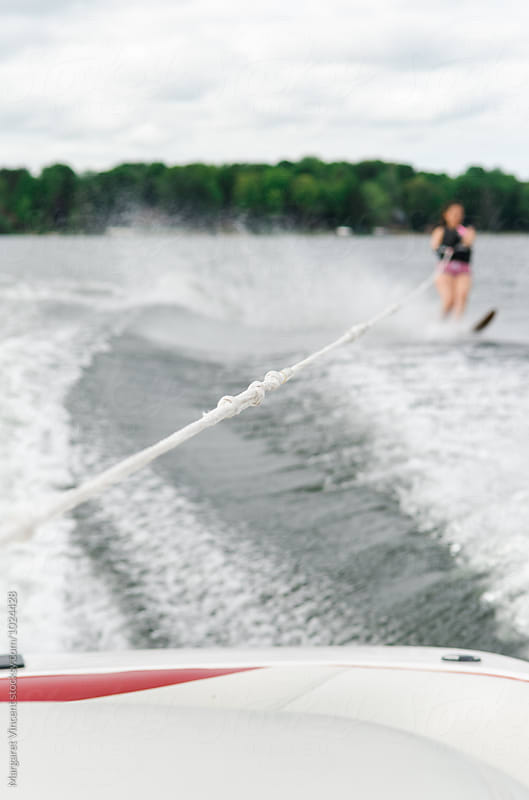 woman water skis, crossing wake by Margaret Vincent for Stocksy United