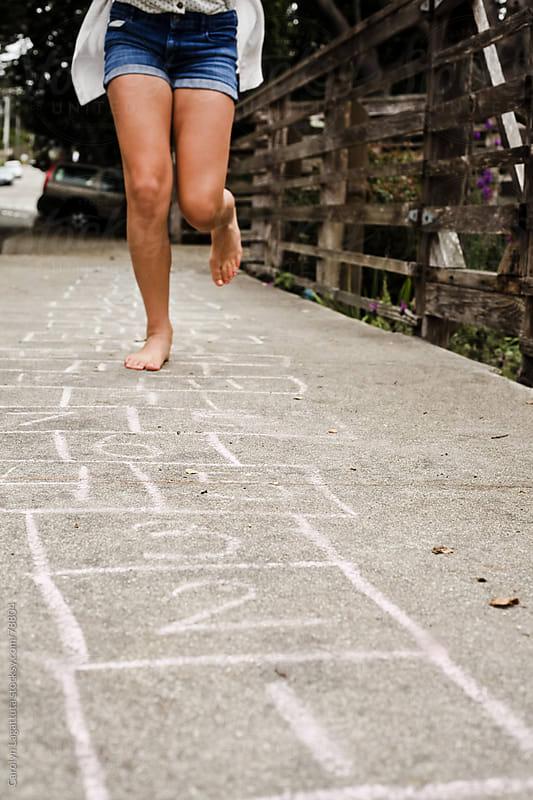 Young girl playing hopscotch on the sidewalk by Carolyn Lagattuta for Stocksy United