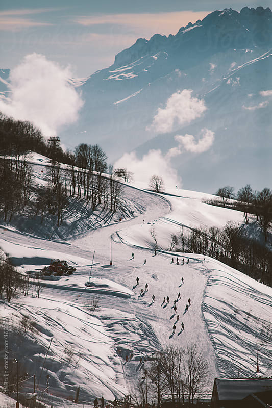 Slopes of a skiresort with the mountains in the background by Ivo de Bruijn for Stocksy United