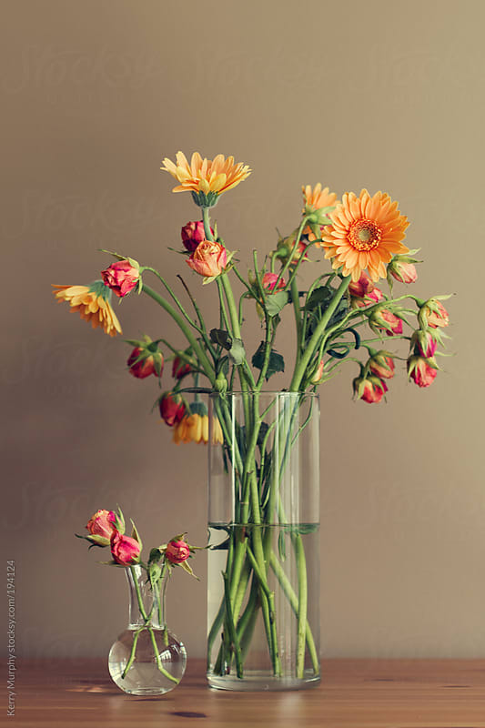 Two vases of gerbera daisy and rose flowers on wooden table by Kerry Murphy for Stocksy United