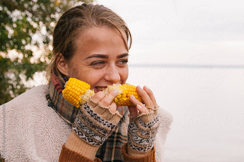 Portrait of girl eating boiled corn in the nature by T-REX & Flower for Stocksy United