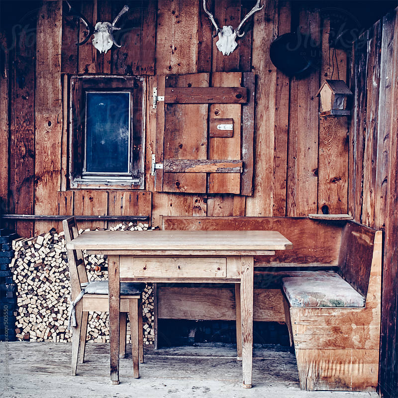 Outside porch of a cozy wooden cabin in the mountains with table and chair by Soren Egeberg for Stocksy United