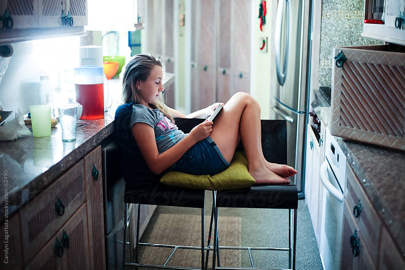 Absorbed in a book in the middle of the kitchen by Carolyn Lagattuta for Stocksy United