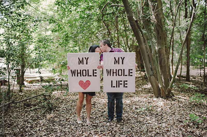 Engaged Couple holding handmade signs by Kristin Rogers Photography for Stocksy United