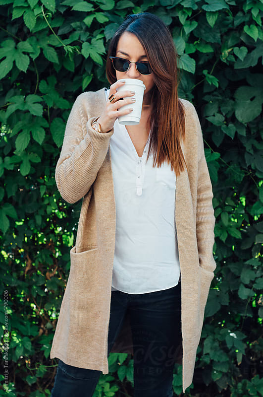 Beautiful young brunette with coffee in front of the foliage background by Dimitrije Tanaskovic for Stocksy United