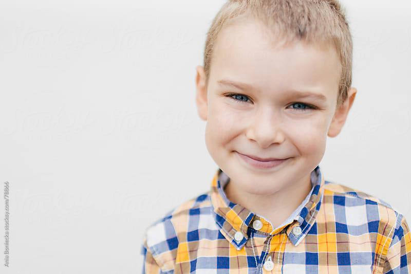 A portrait of a happy boy wearing a plaid shirt by Ania Boniecka for Stocksy United