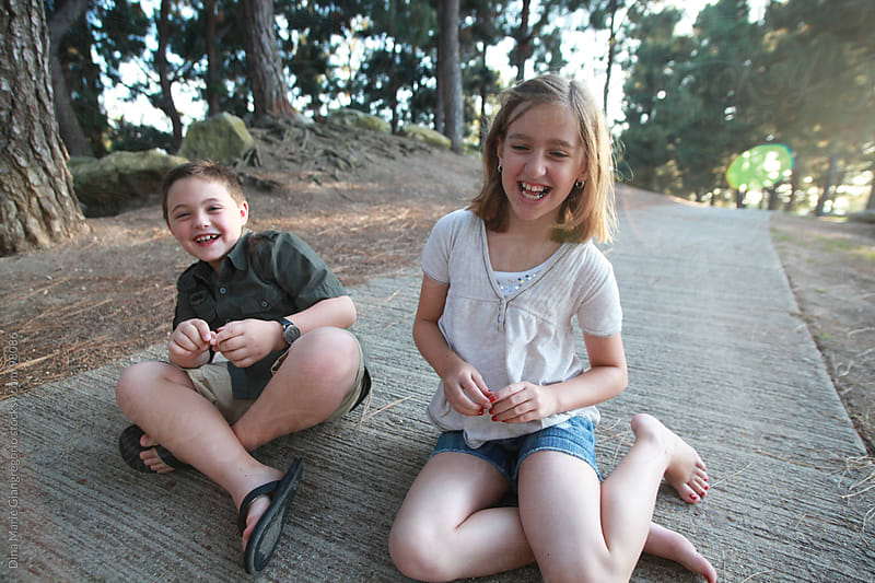 young boy and girl sitting in park laughing by Dina Giangregorio for Stocksy United