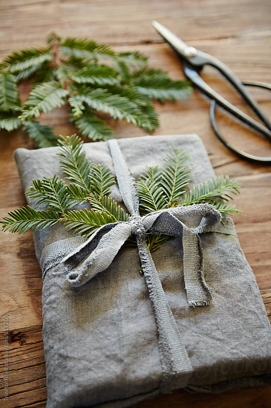 Still life of homemade linen wrapped present with pine branch by Trinette Reed for Stocksy United