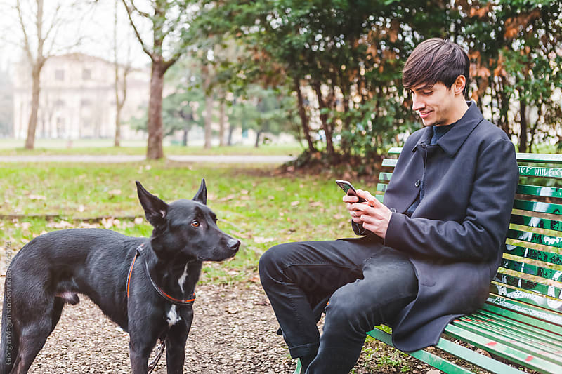 Man with Dog Using the Smartphone at the Park during the Cold Season by Giorgio Magini for Stocksy United