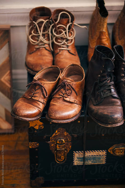 Closeup of old worn leather shoes and boots by Trinette Reed for Stocksy United