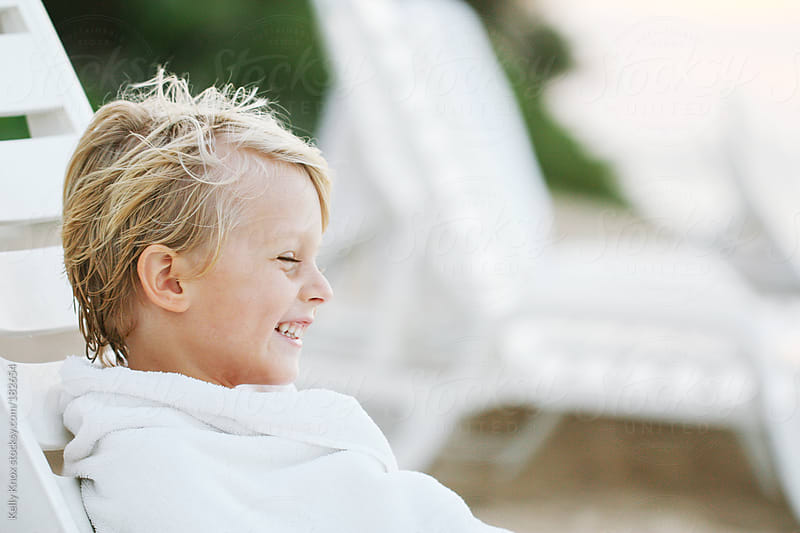 happy boy wrapped in a towel  by Kelly Knox for Stocksy United